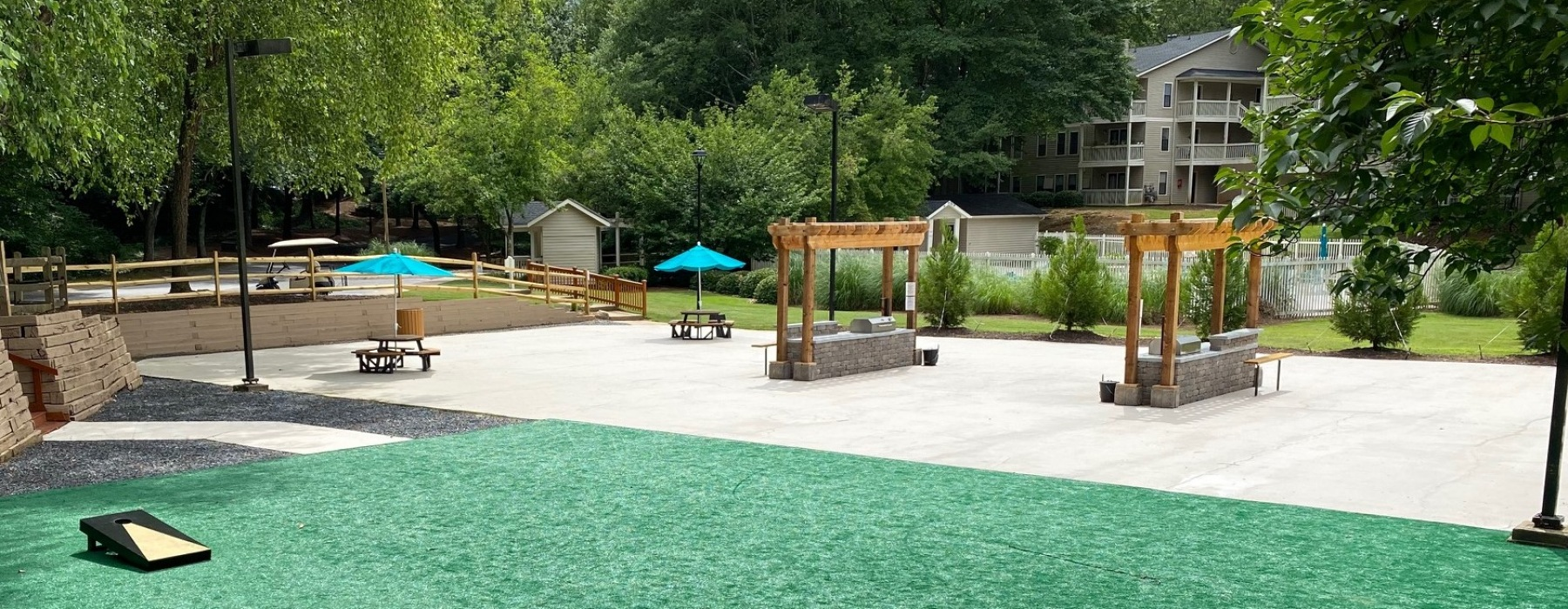 Large patio with artificial grass, corn hole game, pergolas, and lounge furniture