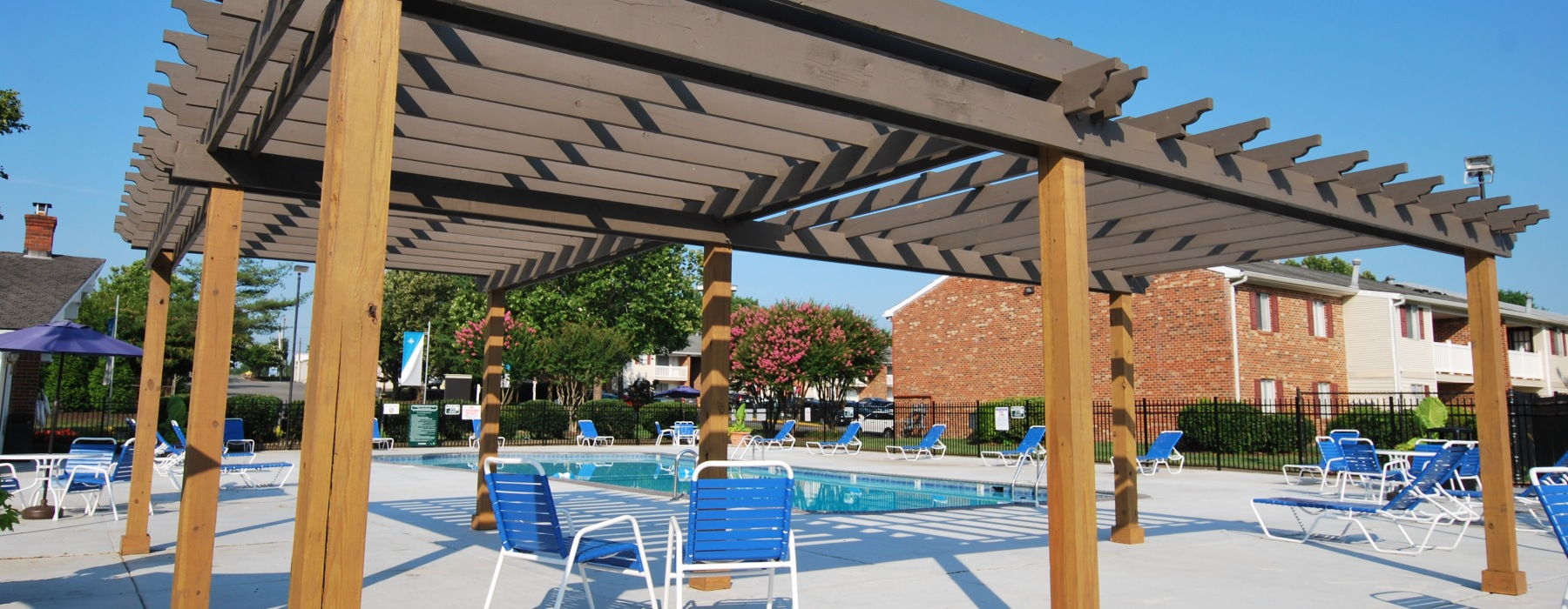 Large wooden pergola overlooking a crystal blue swimming pool