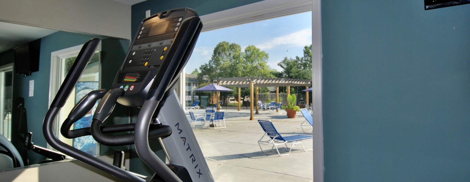Cardio machine with a window view of the pool deck