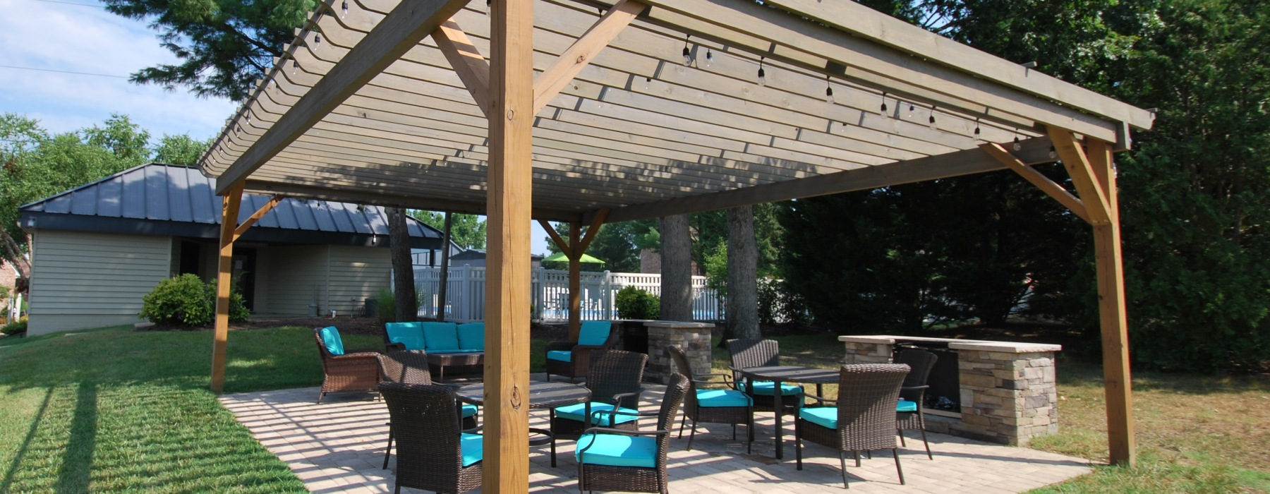 Large pergola with two stone clad grills and string lights