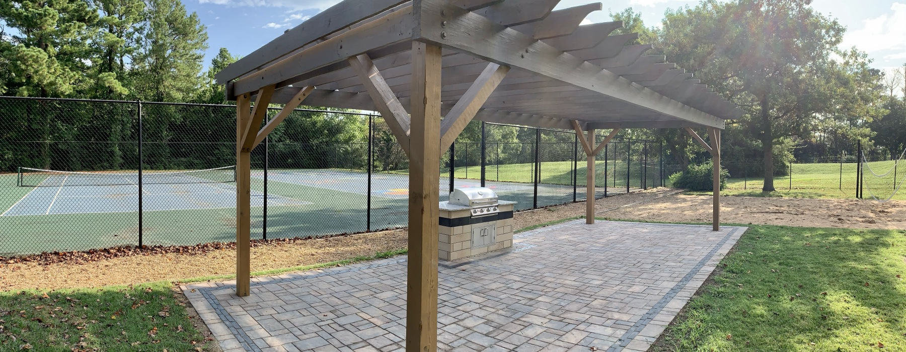 Social grilling terrace with pergola, tennis courts, and vollyeball court