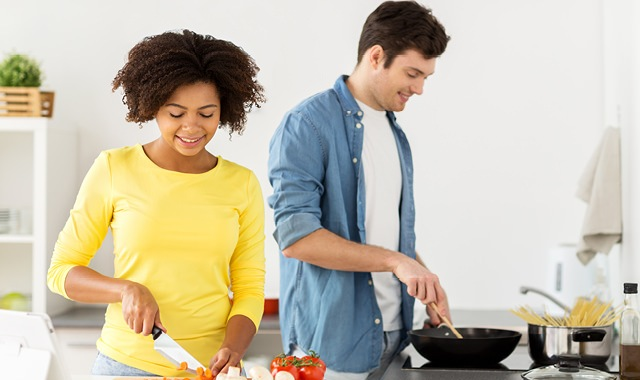 young couple preparing dinner in their apartment home