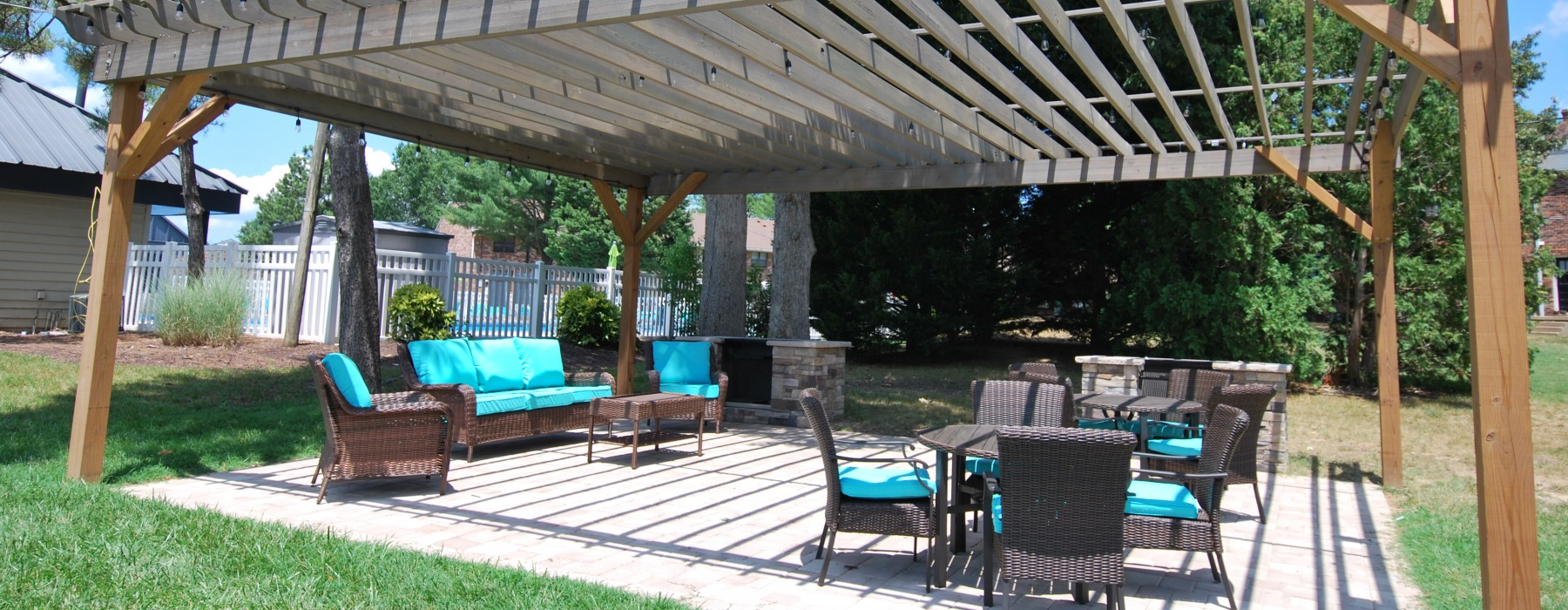 Grill area with lounge furniture covered by pergola