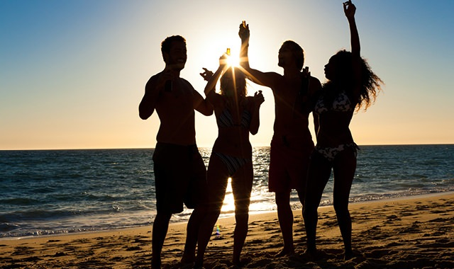 silhoutte of young people jumping in the air on a beach