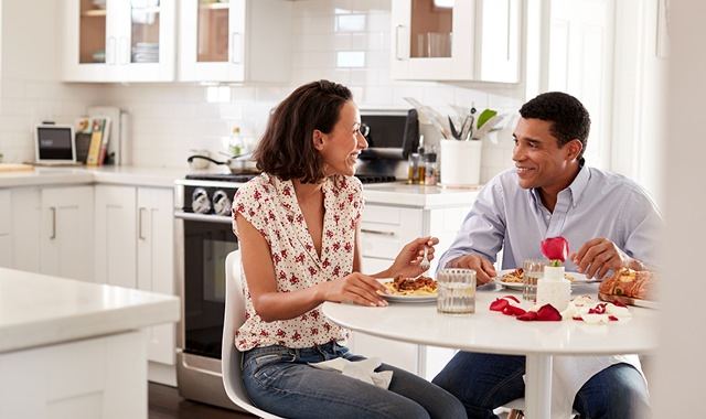 couple happily eating breakfast at their kitchen table