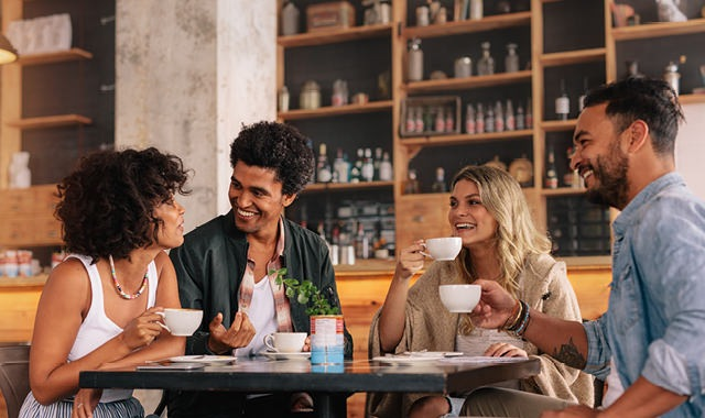 group of young adults smiling around a table over coffee in an urban cafe