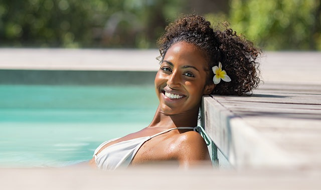 ethnic woman smiling and relaxing in pool