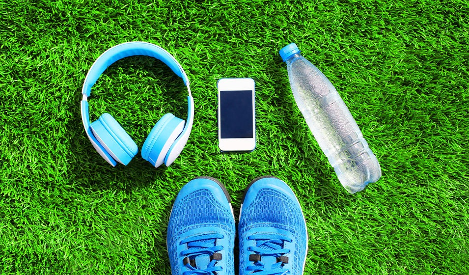 A set of headphones, smart phone, water bottle and tennis shoes