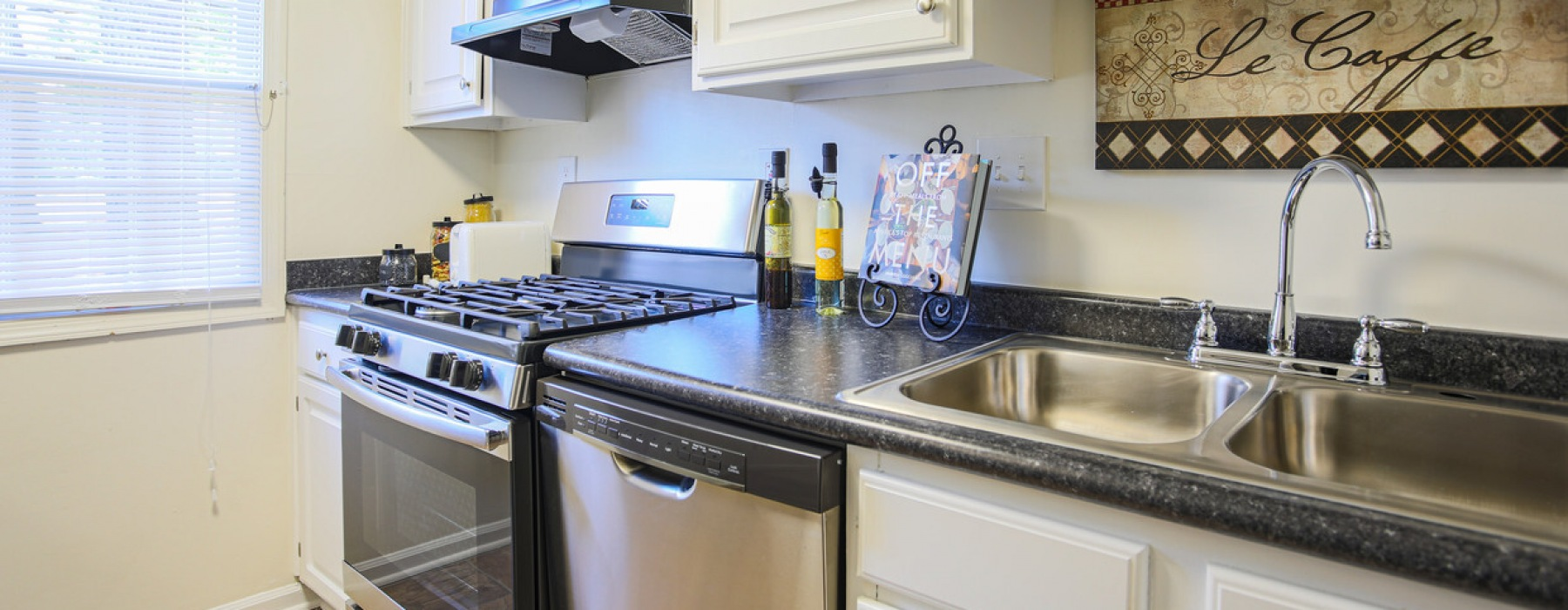 A kitchen with stainless steel appliances, gooseneck faucet, and double basin sink