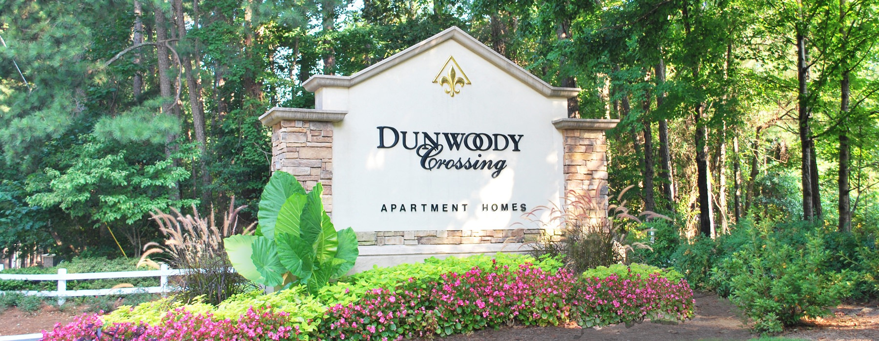 brick and concrete Dunwoody Crossing signage in well landscaped foliage