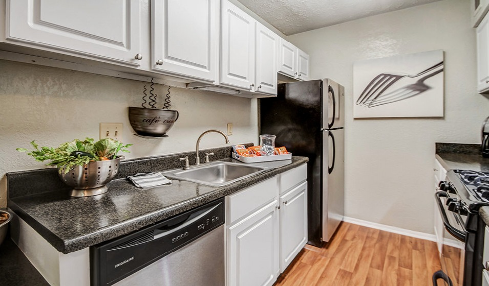 bright, galley kitchen with stainless steel appliances