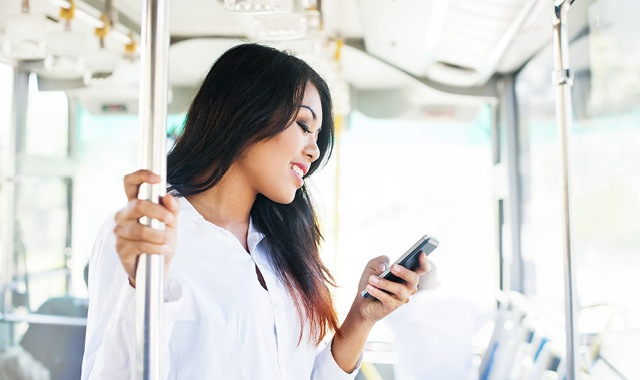 woman standing in empty bus, looking at her phone