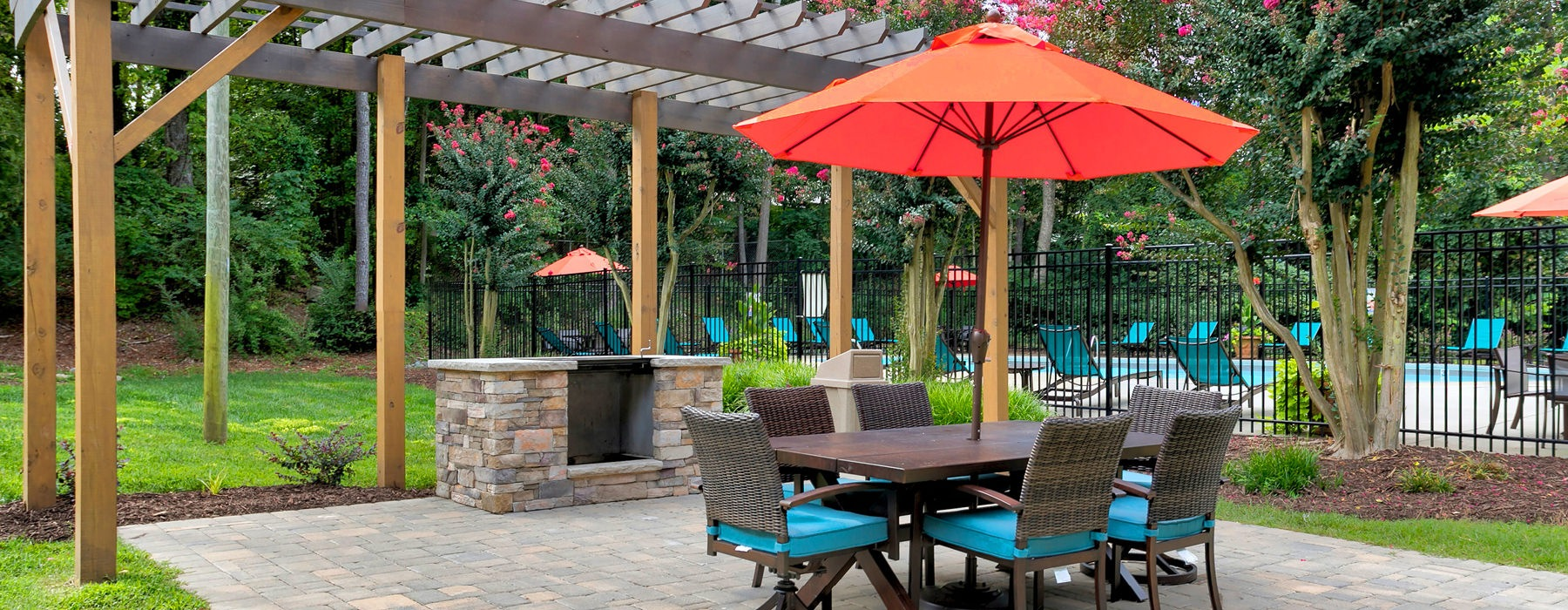 outdoor patio area with wicker chairs surrounding an umbrella covered table