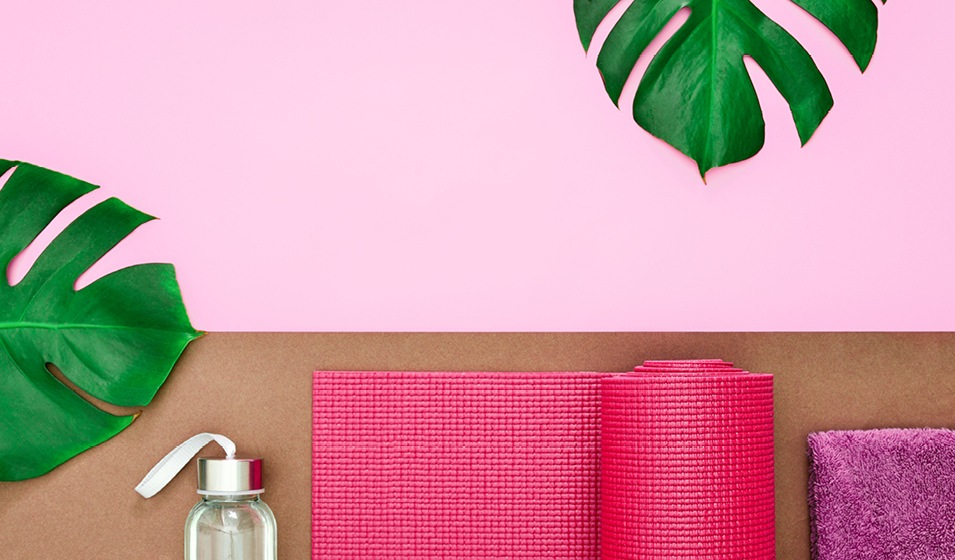yoga mat, towel and water bottle resting on table and framed by large leaves