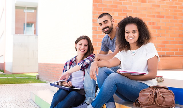 college students sitting on campus steps with notebooks, smiling at the camera
