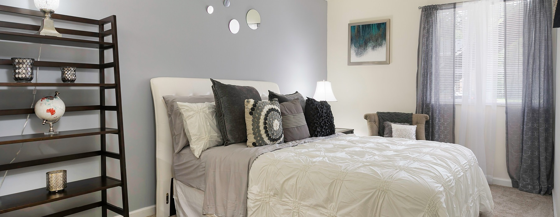spacious, brightly lit bedroom with accent wall