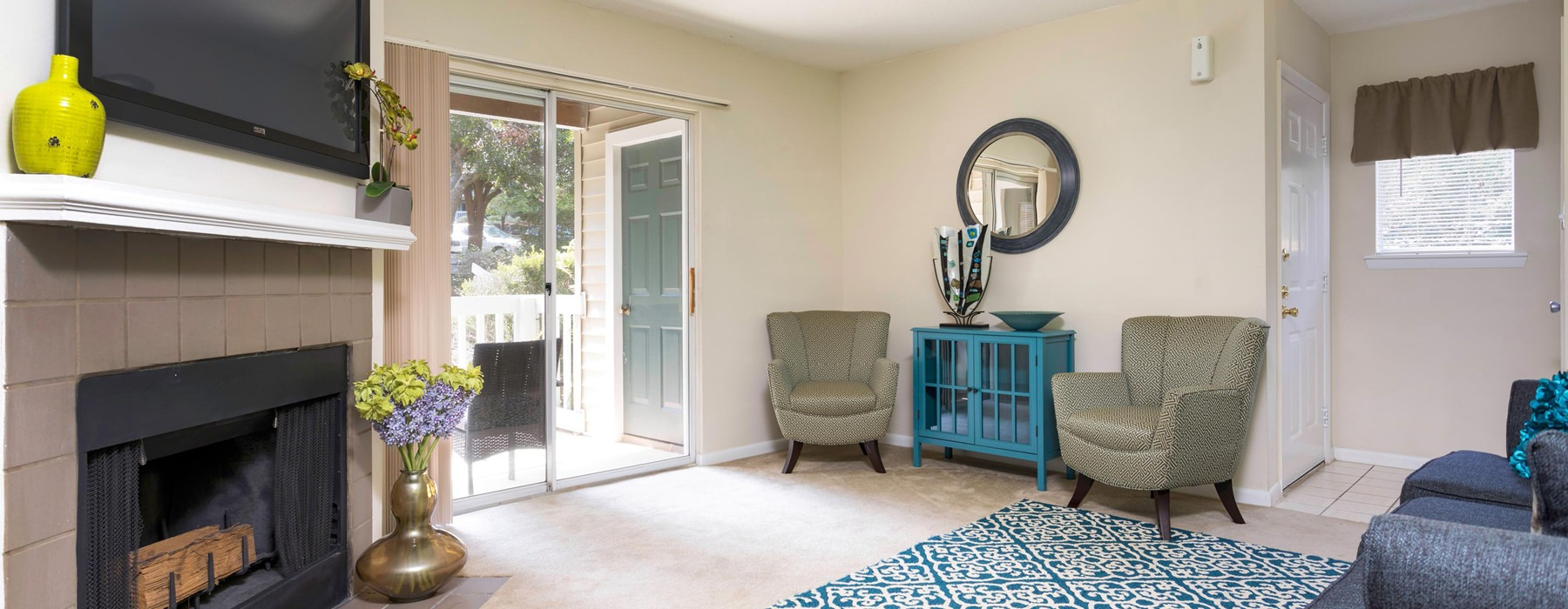 fireplace in brightly lit living room and private porch storage closet
