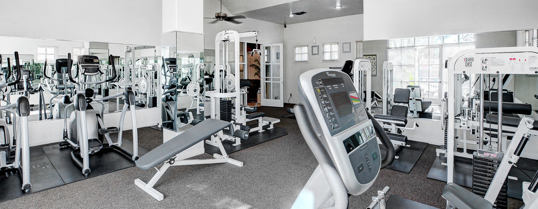brightly lit gym with ceiling fans and central ac