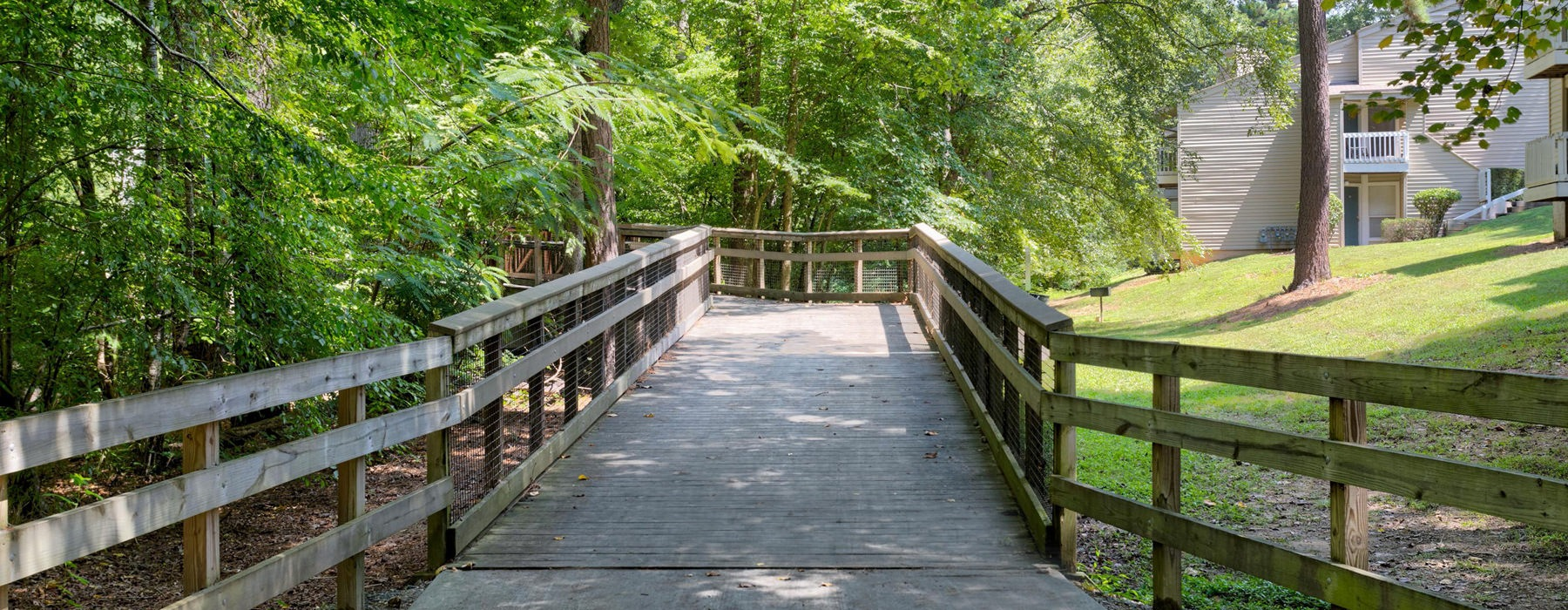 wooden bridge through forested walking trail adjacent to Bryn Athen at Six Forks