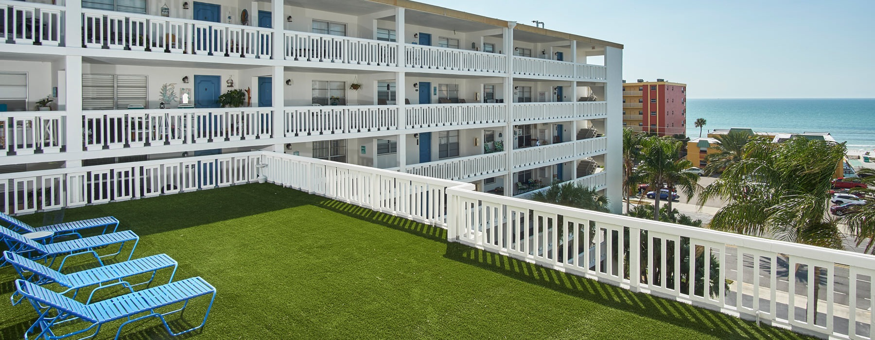 open rooftop deck with grass and lounge chairs with harbor views