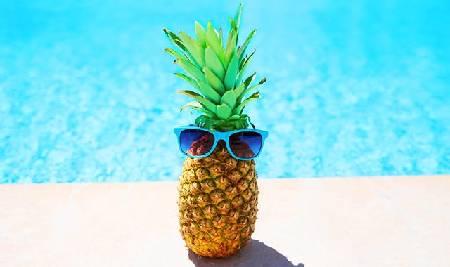pineapple with sunglasses near pool