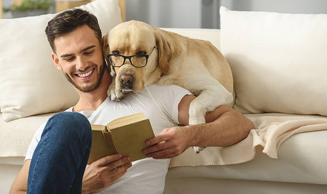 man sits against couch reading a book while dog with glasses looks over his shoulder