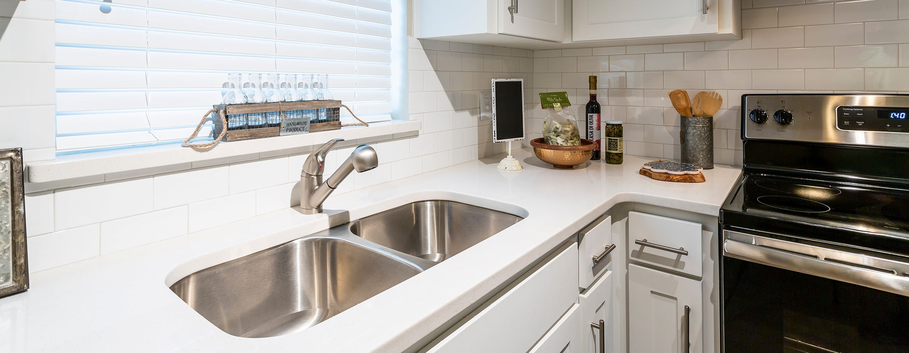 white counter and cabinets in well lit kitchen with window