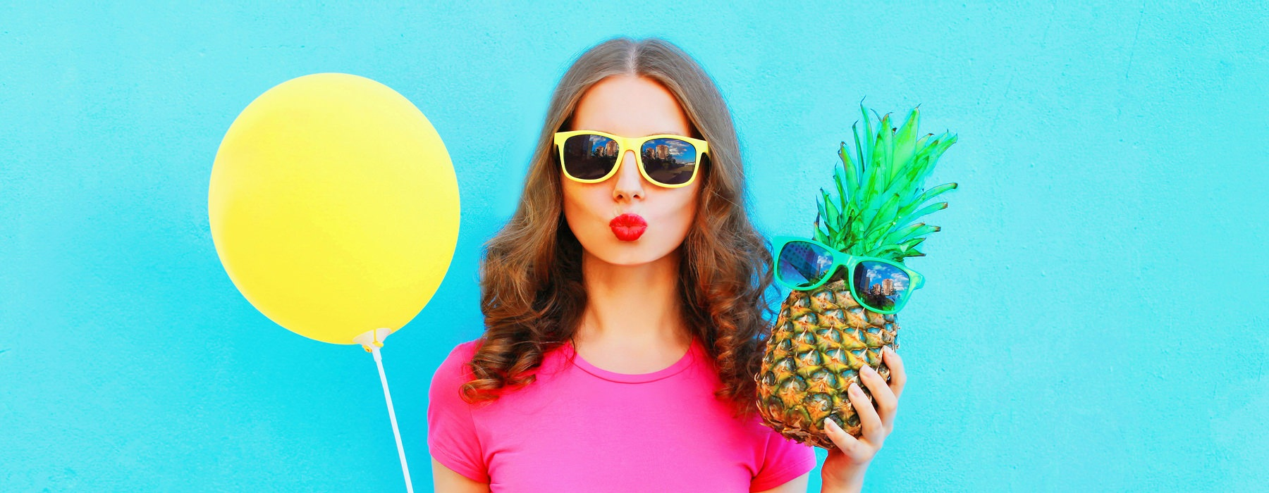 Woman holding a pineapple and yellow balloon