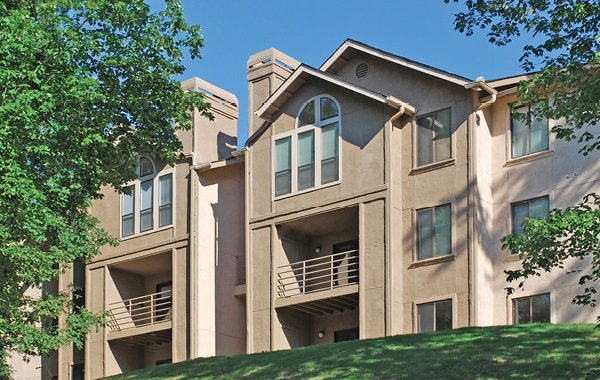 apartment exterior with balconies facing landscaped lawns and wooded area
