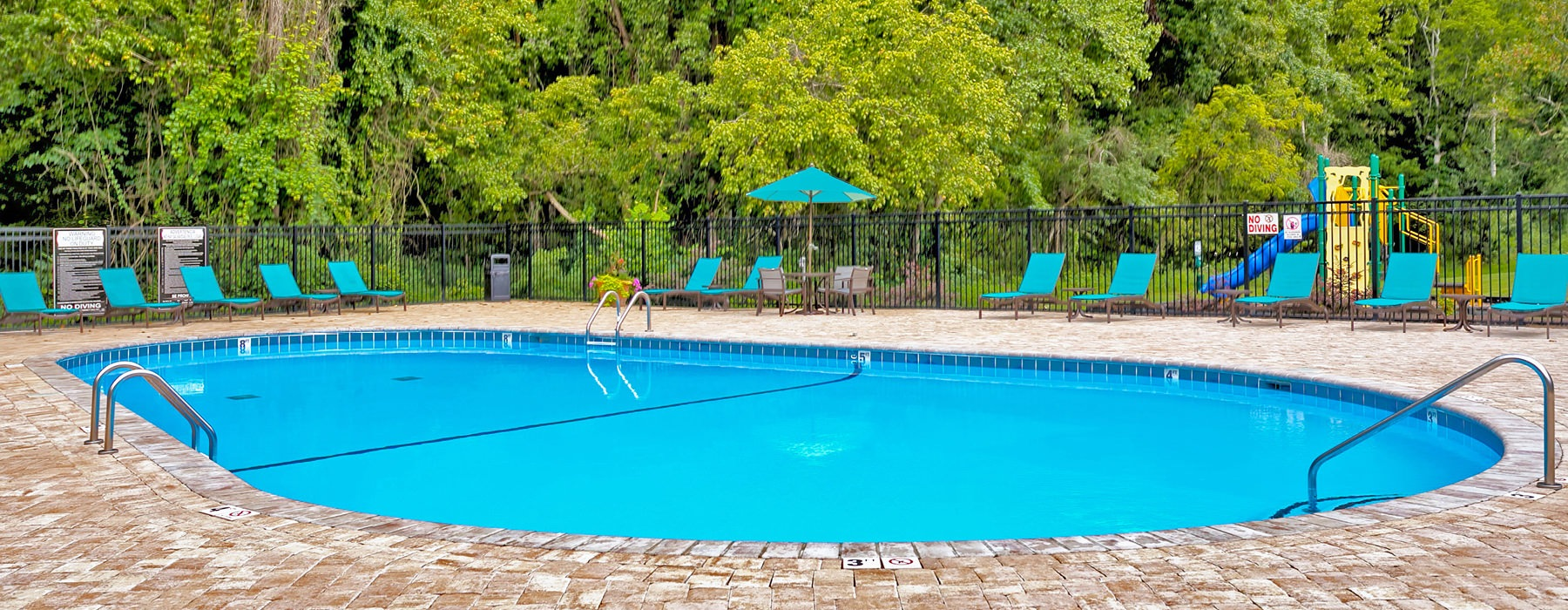 fenced in pool area with umbrella shaded tables and chairs