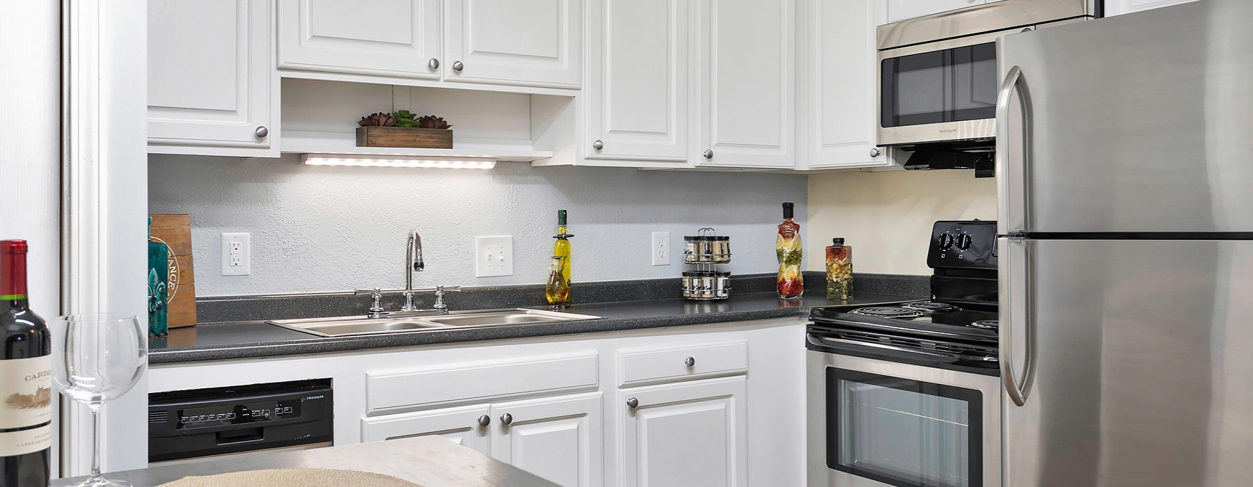 brightly lit kitchen with white cabinetry