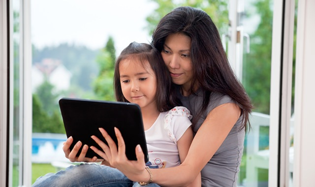 daughter sitting in her mother's lap as they look at a tablet in front of a picture window