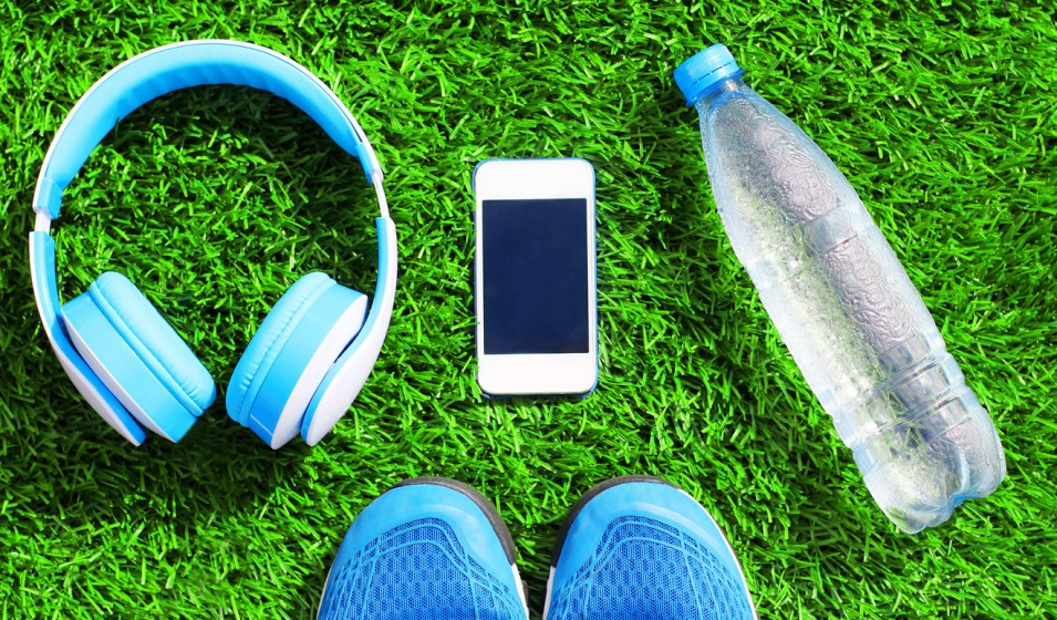 Flatlay of headphones, smart phone, water bottle and tennis shoes