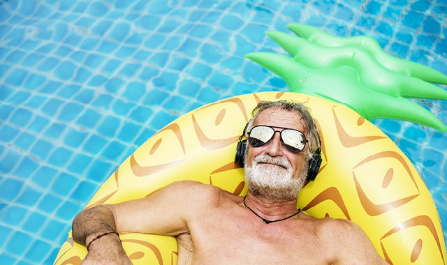 older man relaxes on pineapple shaped floaty in pool