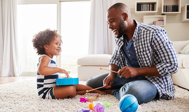young father and child playing on living room carpet