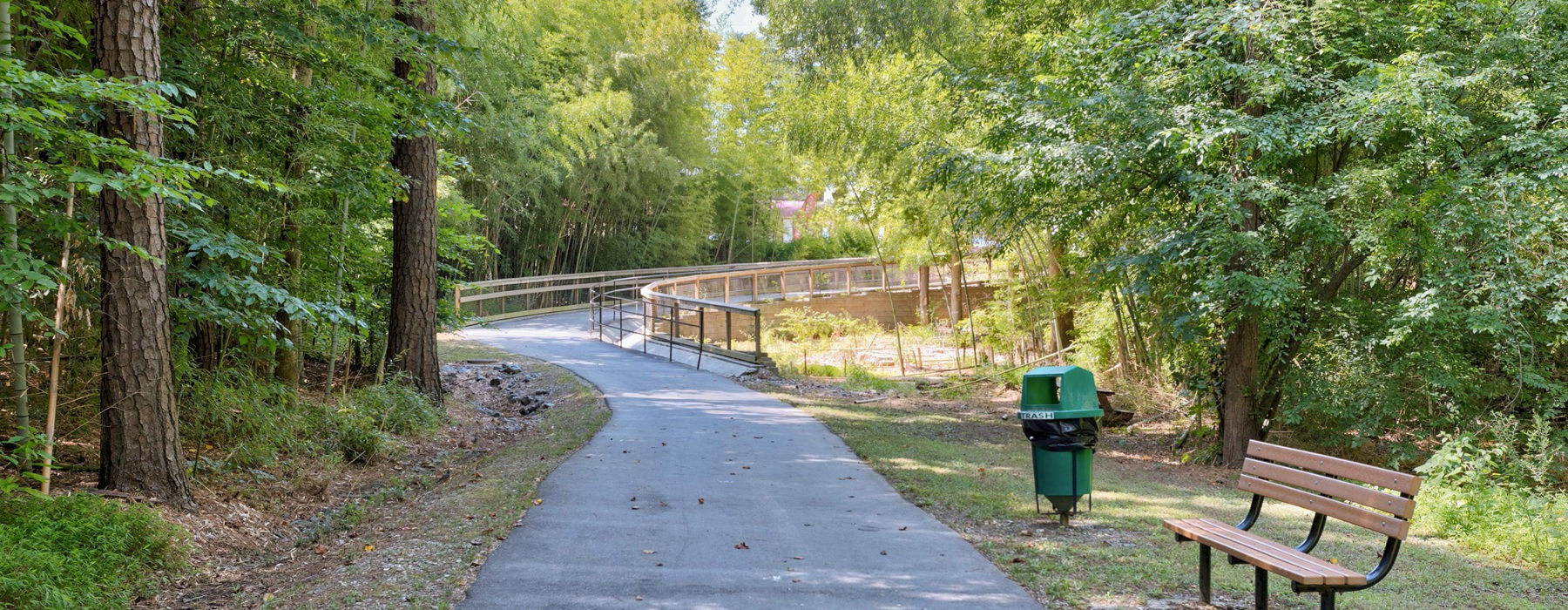 wood lined, paved walking trail with park bench and trash bin