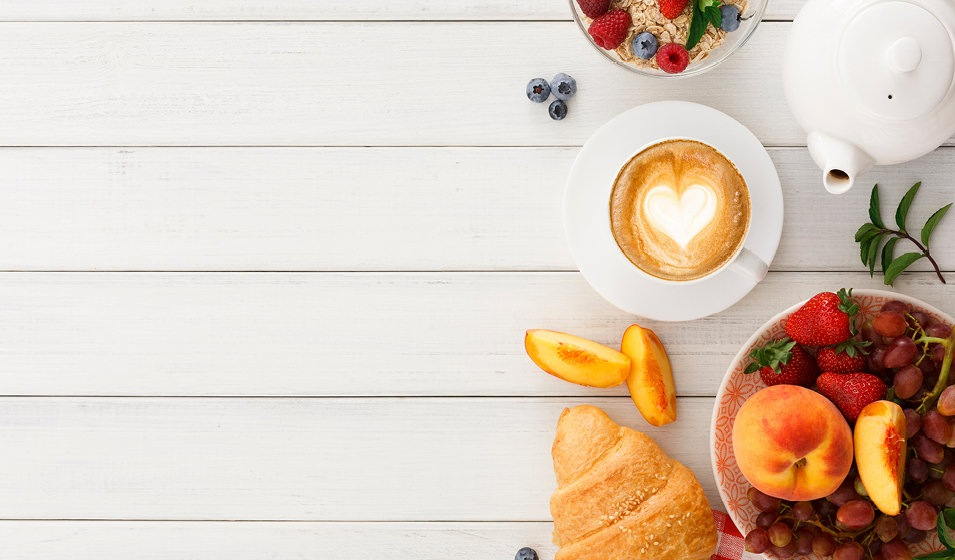 bowls of fruit, cup of coffee, tea pot and croissant on wood table