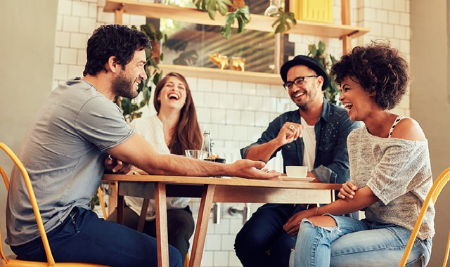 young adult friends laughing around a restaurant table