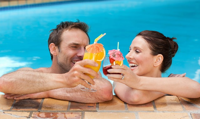 happy couple in the pool with arms resting on the ledge, drinks in hand, as they toast each other