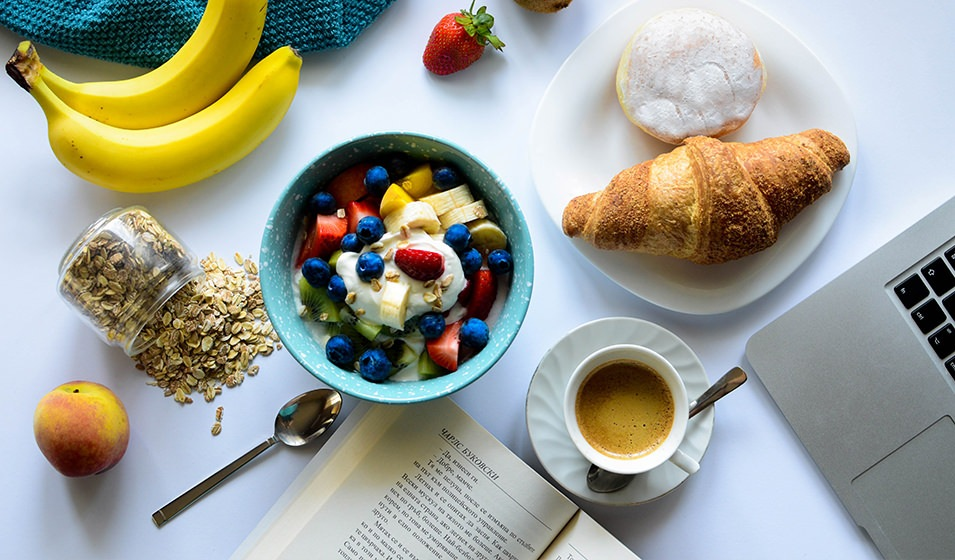 Oatmeal and breakfast food laid out on white marble countertop