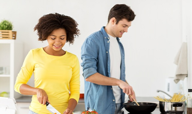 Couple cooking together in a bright kitchen with open countertops