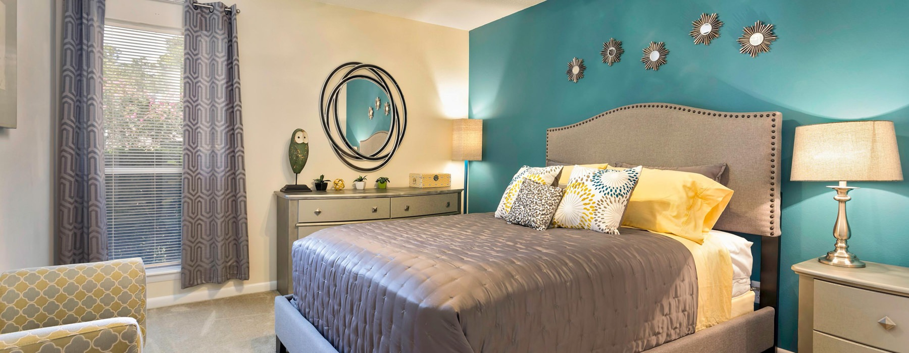 well lit bedroom with accent wall, lighted ceiling fan and window