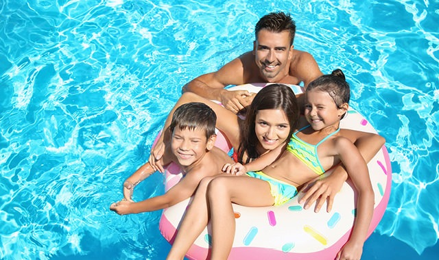 ethnic family smiling up at the camera as they float in pool
