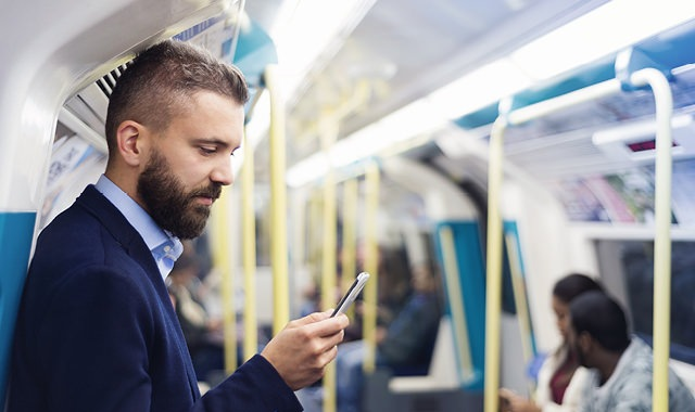 man commuting to work on bus as he looks at phone