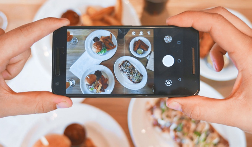 person taking a picture of lunch spread with their phone