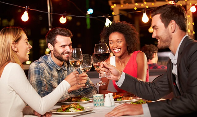 happy, young adults toasting a night out at an outdoor venue