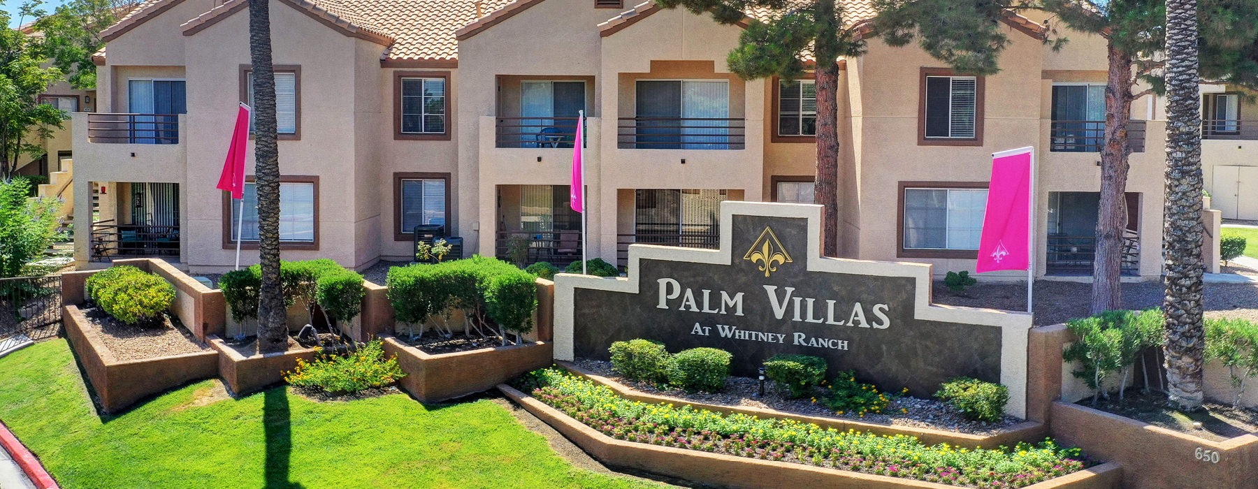 landscaped palm villas entrance with large stone sign and flags