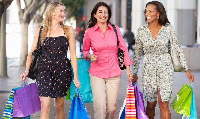 three smiling women walking down the sidewalk with shopping bags