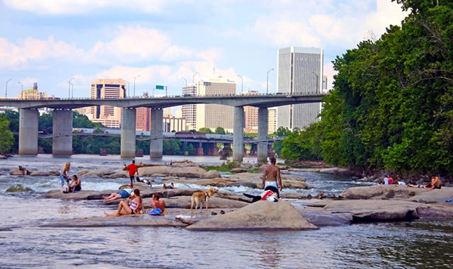 people laying out on rocks near the banks of the river with bridge and city skyline behind them