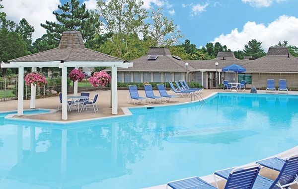 large outdoor pool with cabana, tables and chairs